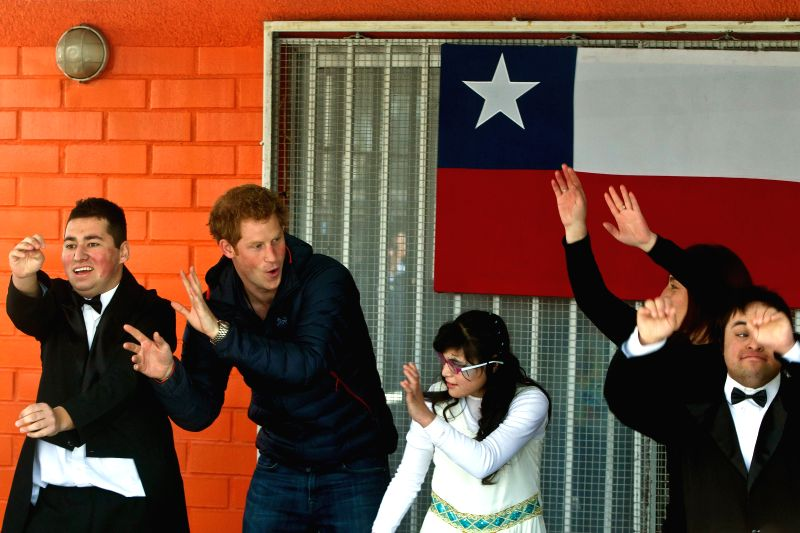Prince Harry (2nd L) of Britain dances during his visit to the Friends of Jesus Foundation in Santiago, capital of Chile, on June 29, 2014. Prince Harry is on a ...