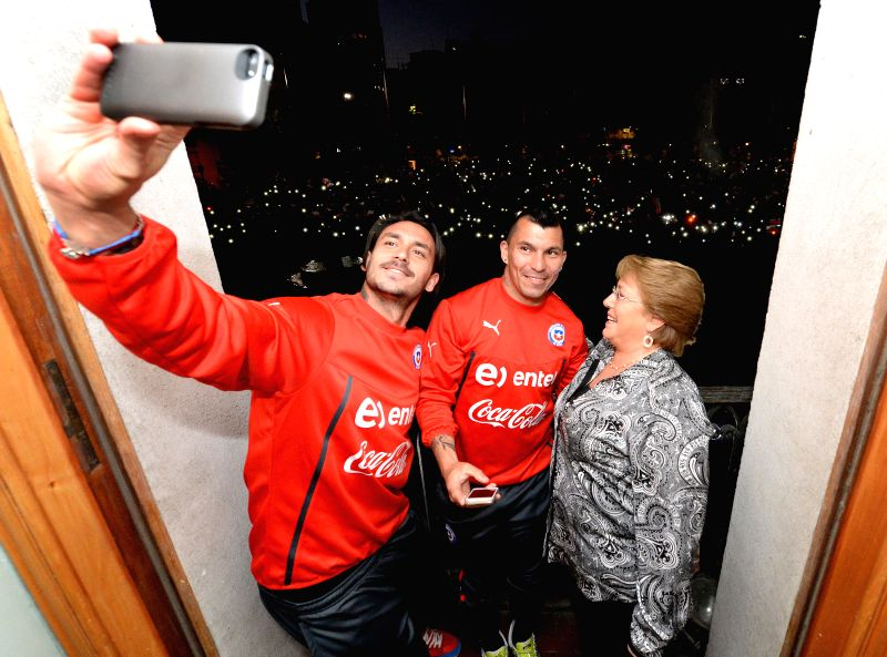 Image provided by Chile's Presidency shows Chilean President Michelle Bachelet (R) poses with players of Chile's National Team at Presidential Palace in the city ..