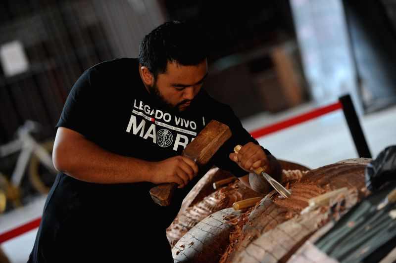 "A man of the Maori culture, carves a wood sculpture during the exhibition ""Tuku Iho: Legacy Live"" at the Cultural Center of Gabriela Mistral, in ..."