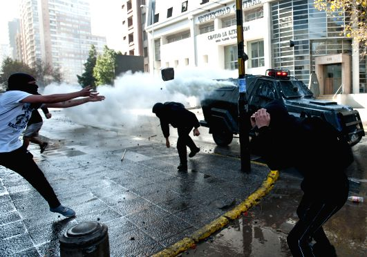 Photo: Students clash with anti-riot policemen during a demonstration, in Santiago, capital of Chile, on May 8, 2014. Students demanded their direct participation in