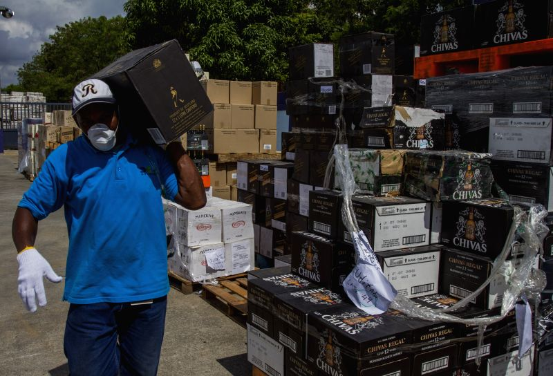 An employee of the Customs General Direction (DGA, for its acronym in Spanish), carries a seized liquor box, in Santo Domingo, Dominican Republic, on July 31, .