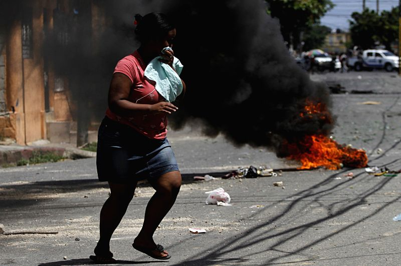 A woman walks in front of a burning tire, during a protest in the Capotillo neighborhood, in Santo Domingo, Dominican Republic, on Aug. 27, 2014. The ...