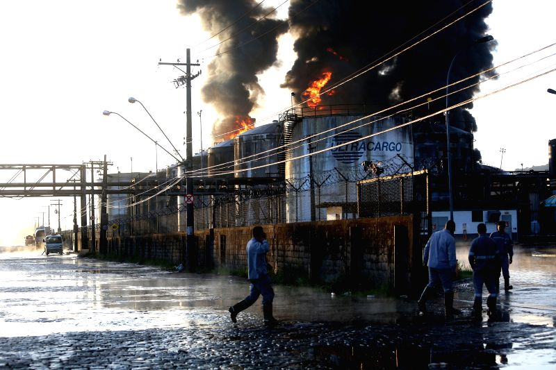 A smoke column rises from a liquid storage facility of Ultracargo, one of the major liquid storage companies of Brazil, in Santos, Brazil, on April 3, 2015. The fire ...