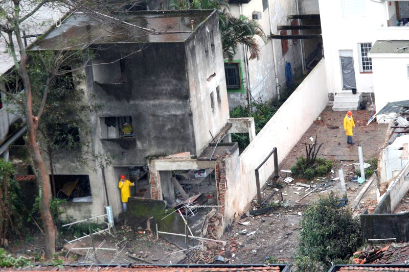 Emergency personnel inspect the crash site of the aircraft carrying the presidential candidate for the Socialist Party of Brazil Eduardo Campos in a residential zone