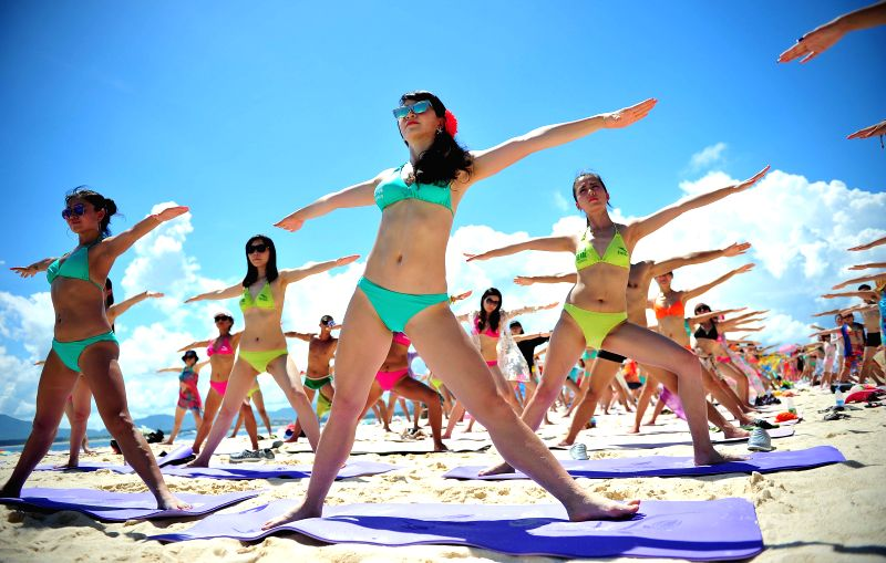 People practice yoga during a massive bikini party held at the Wuzhizhou Island in Sanya, south China's Hainan Province, July 12, 2014.