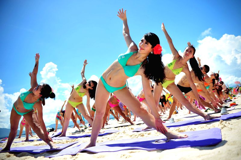 People practice Yoga during a seaside bikini festival on Wuzhizhou Island of Sanya, south China's Hainan Province, July 12, 2014.