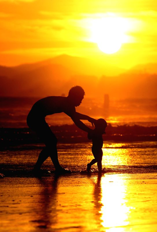 A child and his parent play on the seashore at sunset in Sanya, south China's Hainan Province, June 18, 2014.
