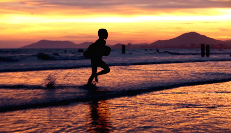 A child plays on the seashore at sunset in Sanya, south China's Hainan Province, June 18, 2014.