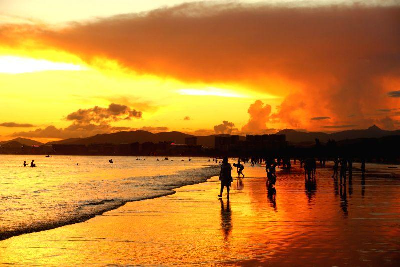 SANYA, June 25, 2016 - People wander amid sunset glow by the sea in Sanya, south China's Hainan Province, June 23, 2016.