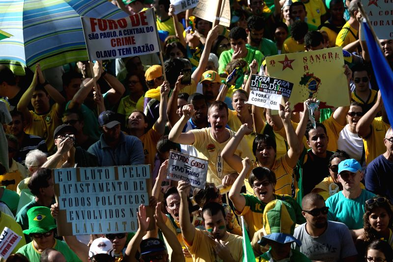 Residents take part in the demostration against the government of Brazilian President Dilma Rousseff after allegations of corruption in the state oil company ...
