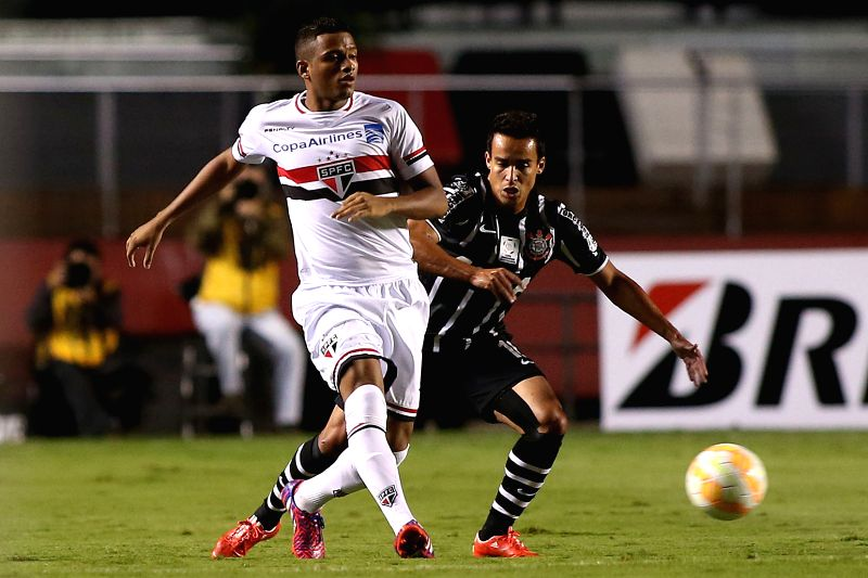 Sao Paulo's Reinaldo (L) vies with Corinthians' Jadson during the match of Copa Libertadores in Sao Paulo, Brazil on April 22, 2015.