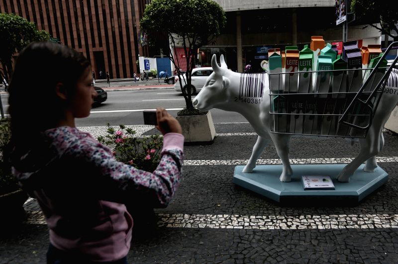 SAO PAULO, April 28, 2017 - A person takes a photo for a fiber-glass painted cow, as part of the Brazil's 10 CowParade, in Sao Paulo, Brazil, on April 27, 2017. According to local press, the ...