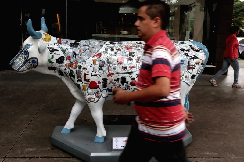 SAO PAULO, April 28, 2017 - A person walks past a fiber-glass painted cow, as part of the Brazil's 10 CowParade, in Sao Paulo, Brazil, on April 27, 2017. According to local press, the CowParade is a ...