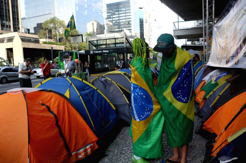 SAO PAULO, April 5, 2016 - People walk through a camp of demonstrators who are in favor of impeachment against Brazilian President Dilma Rousseff, in Sao Paulo, Brazil, on April 4, 2016.