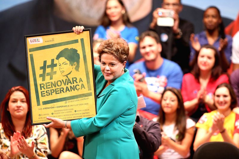 Brazil's President and Presidential Candidate, Dilma Rousseff holds an image during an electoral campaign event, in Sao Paulo, Brazil, on Aug. 11, 2014. The ...