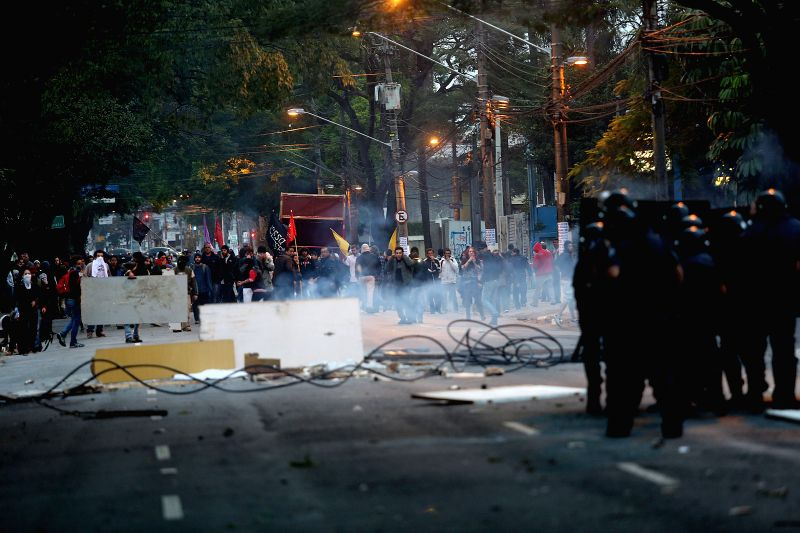 Police officers are confronted with workers and students of Sao Paulo University (USP), during a strike and protest in Sao Paulo, Brazil, on Aug. 20, 2014. The ...