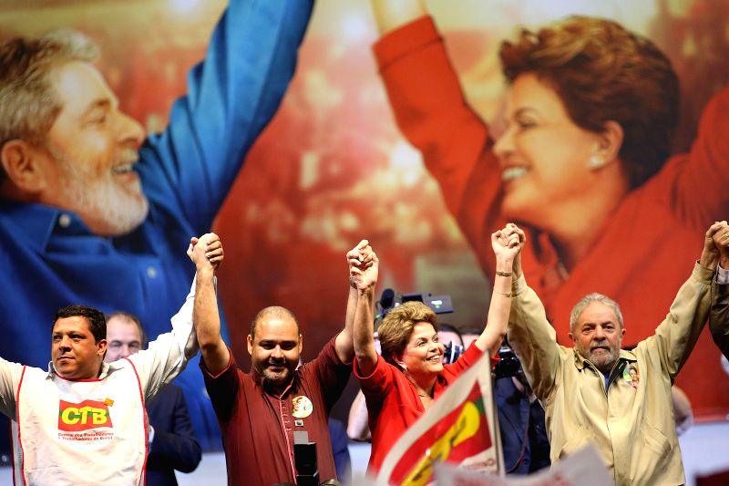 Brazilian President Dilma Rousseff (2nd R) and former President of Brazil Luiz Inacio Lula da Silva (1st R) hold hands during a campaign event in Sao Paulo, ...