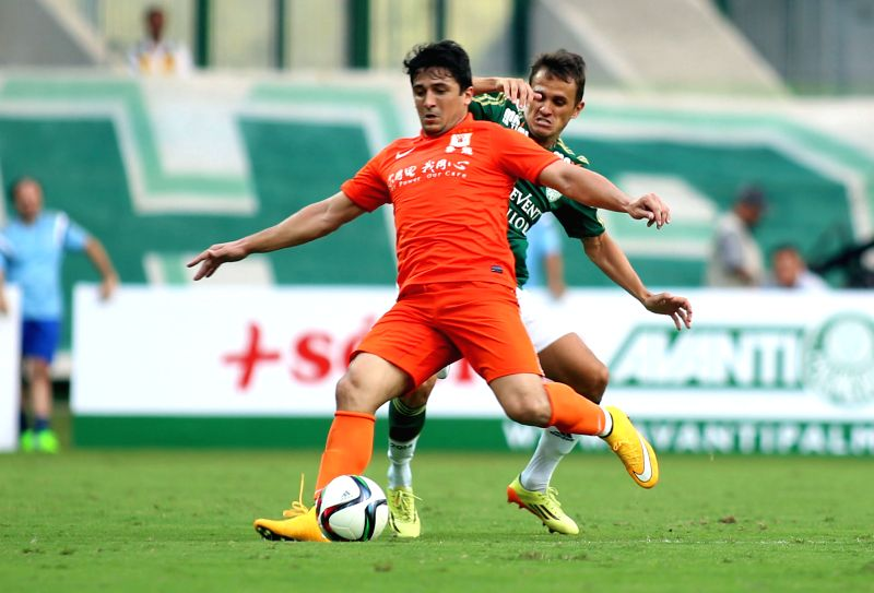 Aloisio (Front) of China's Shandong Luneng vies with Lucas of Brazil's Palmeiras during a friendly match at the Allianz Park Stadium in Sao Paulo, Brazil, Jan. ...