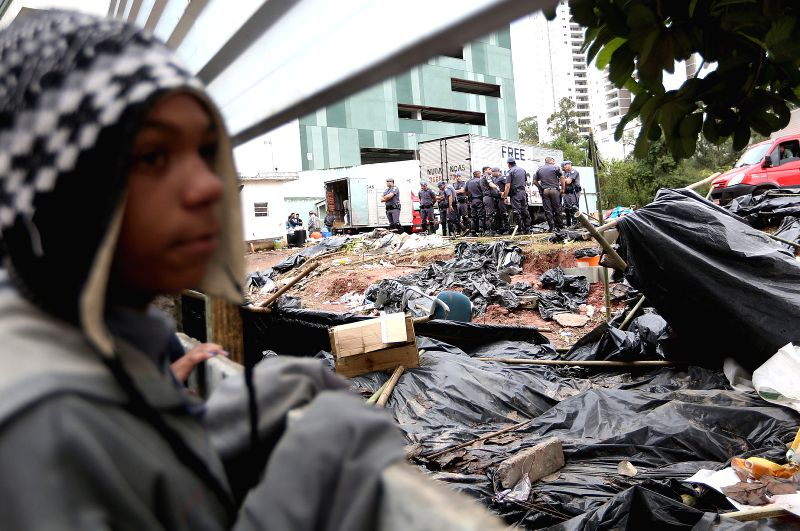 A child looks on as Policemen evict homeless people from a private lot near the Arena de Sao Paulo Stadium, which has been occupied by 4,000 poor families since ..