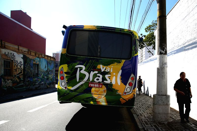 "People walk by the ""Copa Bus"", in Santo Andre, Sao Paulo state, Brazil, on July 2, 2014. The ""Copa Bus"" is a public bus decorated with the ..."