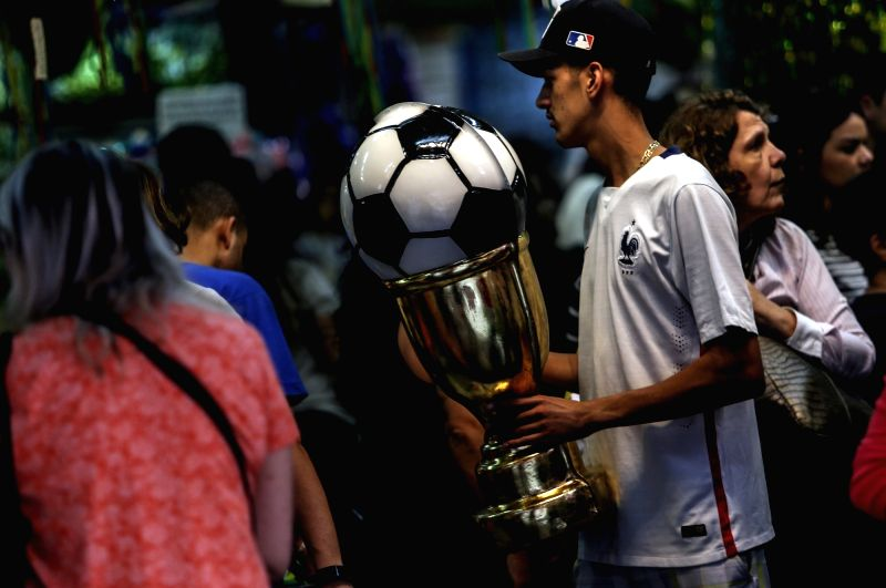 SAO PAULO, June 14, 2018 - A man holds a trophy at a store in Sao Paulo, Brazil, on June 13, 2018. The Russia 2018 FIFA World Cup will be held from June 14 to July 15, 2018.