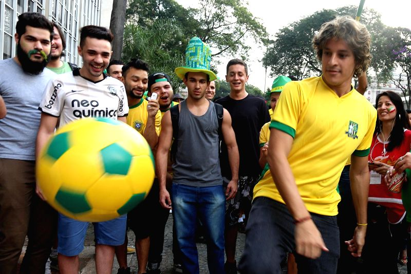 People play soccer prior to a match between Brazil and Mexico, at the FIFA Fan Fest in Sao Paulo, Brazil, June 17, 2014.