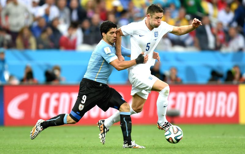 Uruguay's Luis Suarez (L) attempts to hamper the attack of England's Gary Cahill during a Group D match between Uruguay and England of 2014 FIFA World Cup at the .