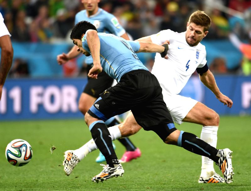 Uruguay's Luis Suarez (L) vies with England's Steven Gerrard during a Group D match between Uruguay and England of 2014 FIFA World Cup at the Arena de Sao Paulo ..