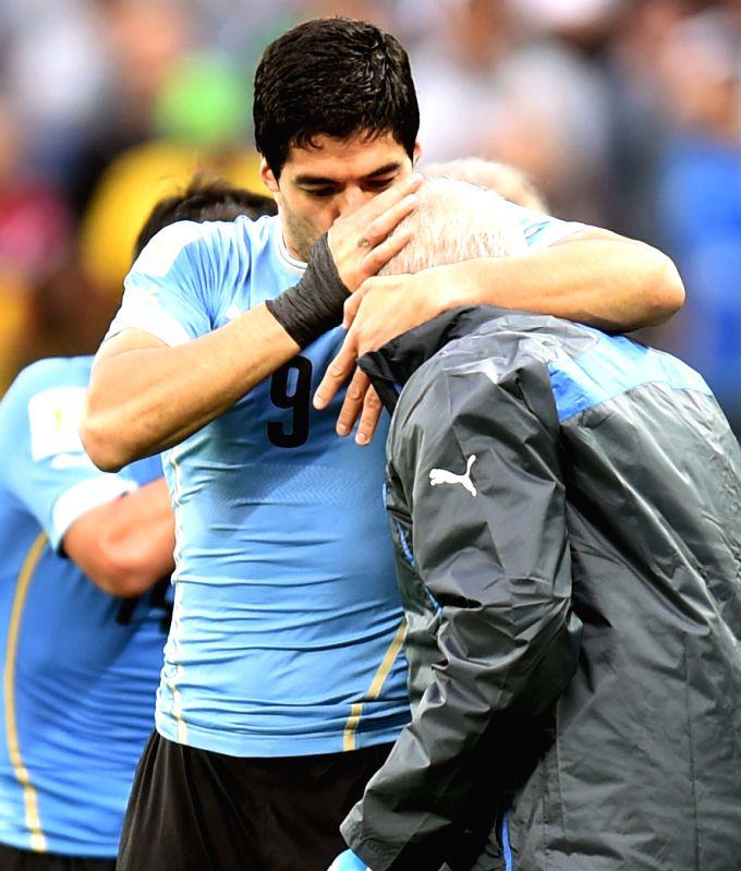Uruguay's Luis Suarez (L) kisses coach Oscar Washington Tabarez during a Group D match between Uruguay and England of 2014 FIFA World Cup at the Arena de Sao ...