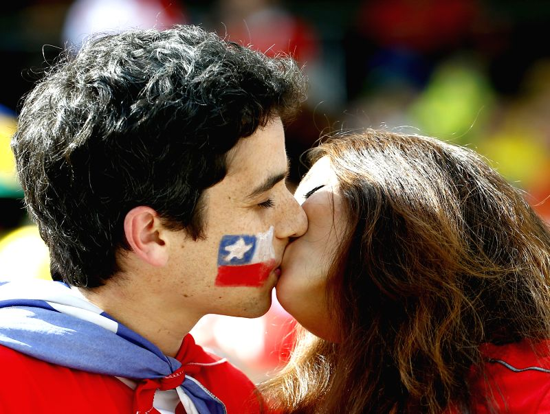 A couple kisses before a Group B match between Netherlands and Chile of 2014 FIFA World Cup at the Arena de Sao Paulo Stadium in Sao Paulo, Brazil, on June 23, ...