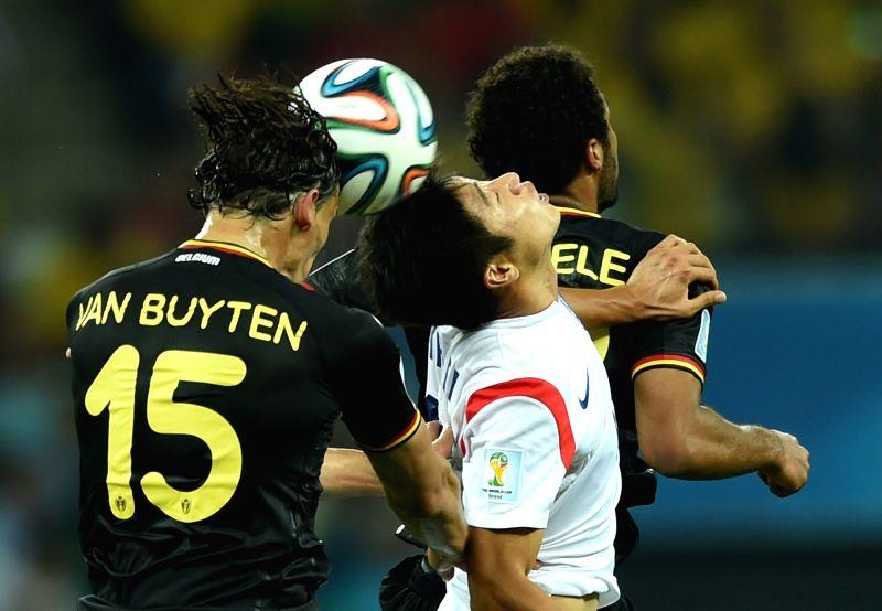 Belgium's Daniel Van Buyten (L) competes for a header during a Group H match between Korea Republic and Belgium of 2014 FIFA World Cup at the Arena de Sao Paulo ..