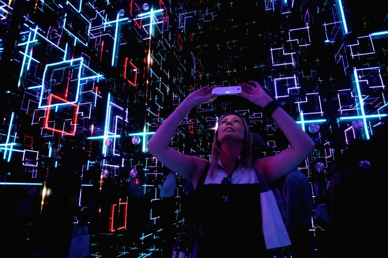 A visitor takes a picture during the exhibition Future Sensations to celebrate 350th anniversary of French multinational corporation Saint-Gobain in the city of ...