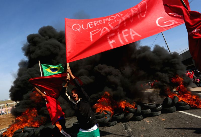 Members of the Homeless Workers' Movement (MTST) take part in a protest against the high cost of the World Cup Brazil 2014, in front of the Arena de Sao Paulo ...