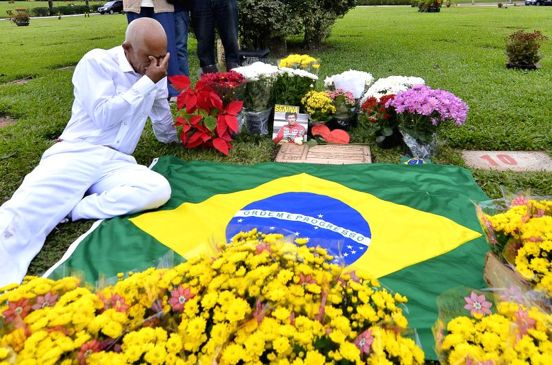 A supporter reacts in front of the tomb of the Brazilian driver, Ayrton Senna da Silva, during the 20th anniversary of his death, in Sao Paulo, Brazil, on May 1, ...