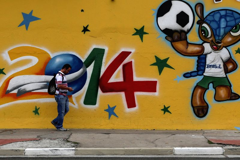 A man rides a bike in front of a wall in the city of Sao Paulo, Brazil, on May 7, 2014. Brazil will face Croatia in the opening match of the FIFA World Cup 2014, in