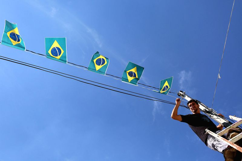 Image taken on May 3, 2014 shows a man decorating a street with Brazil's national flags, as part of the preparatives for the FIFA World Cup Brazil 2014, in Sao ...