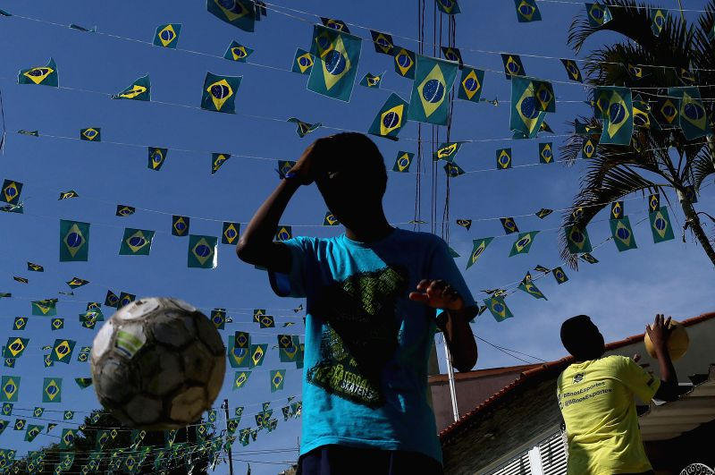 Image taken on May 3, 2014 shows a young man looking on in a decorated street in Sao Paulo, Brazil. Sao Paulo will host the opening match of the FIFA World Cup ...
