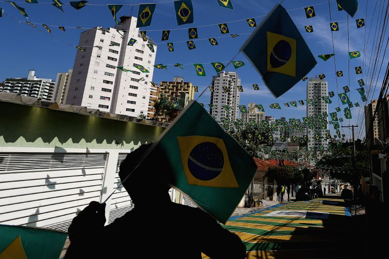 Image taken on May 3, 2014 shows a man decorating a street with Brazil's national flags, as part of the preparations for FIFA World Cup Brazil 2014, in Sao Paulo, ..