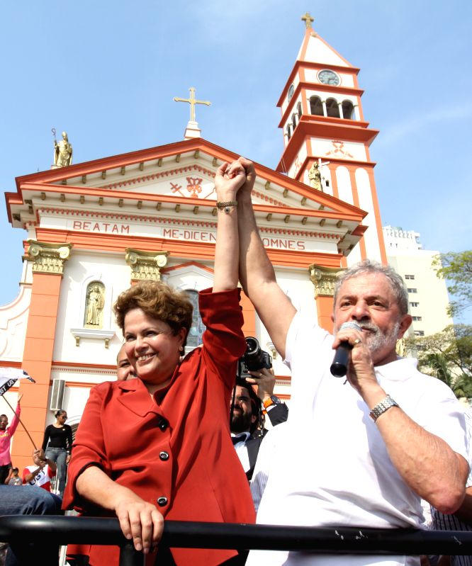 Brazilian former president, Luiz Inacio Lula da Silva (R), holds the hand of Brazil's President and presidential candidate for the Worker's Party, Dilma Rousseff .