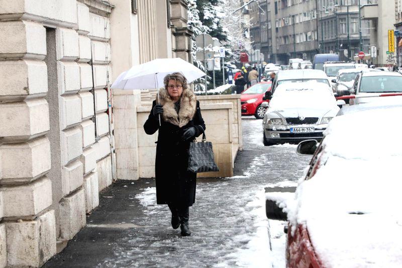 SARAJEVO, Feb. 13, 2018 - A woman walks in snow in Sarajevo, Bosnia and Herzegovina, on Feb. 13, 2018. Snowfall hit Sarajevo here on Tuesday.