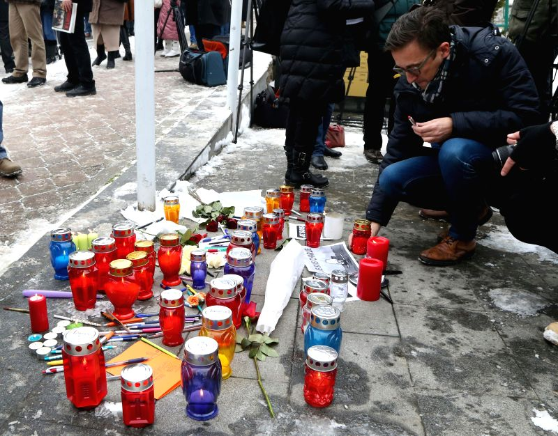 A man lights up a candle and mourns for victims of the January 7 attack against French magazine Charlie Hebdo in front of the French embassy in Sarajevo, Bosnia and