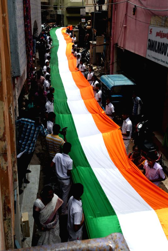 School children carry a 200 feet (61 meters) long Indian national flag through an alley as part of Independence Day celebrations in Chennai on Aug 13, 2014.