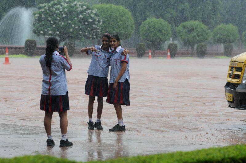 School students enjoy rains in New Delhi on Aug 10, 2014.