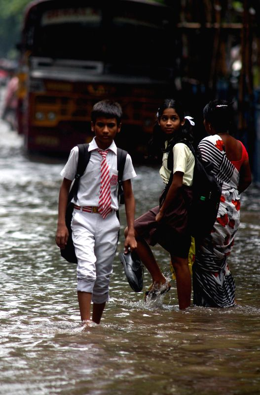 School students enjoy themselves in waterlogged roads of Kolkata after rains on July 1, 2014.