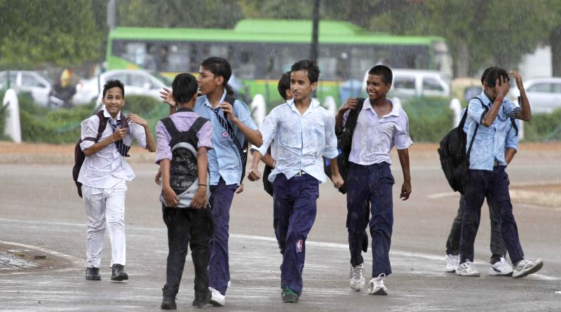 School students enjoy themselves on a Delhi road during rains in the national capital on July 17, 2014.