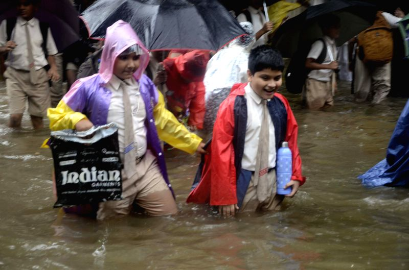 School students play on a waterlogged streets of Mumbai on July 11, 2014.