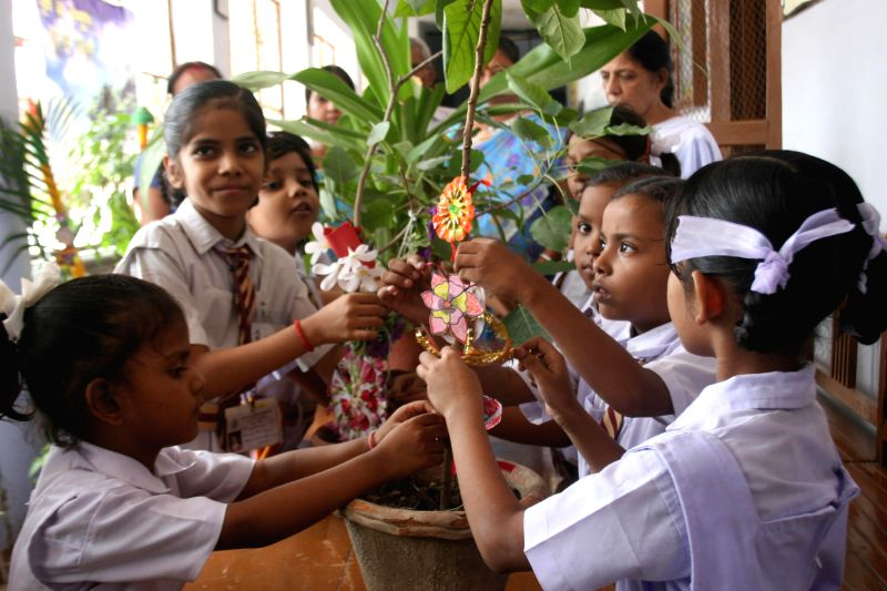 School students tied rakhis to the plants for keep environment clean and healthy on the eve of Rakshabandhan in a school in Varanasi on Aug. 9, 2014.