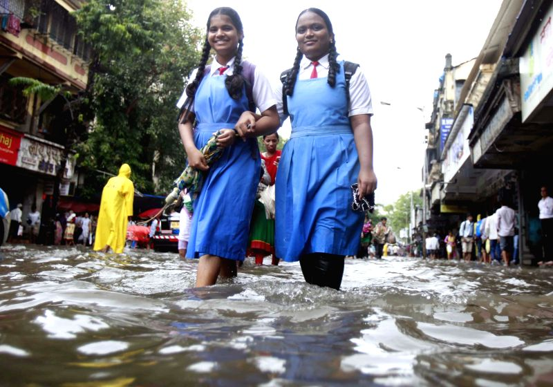 School students wade through flooded streets of  Mumbai after heavy rains in Mumbai on July 16, 2014.