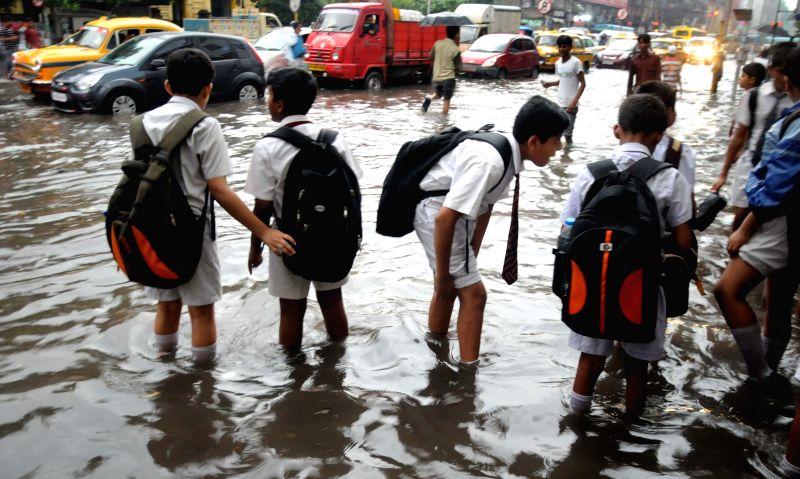 School students wade through water-logged streets of Kolkata on July 2, 2014.