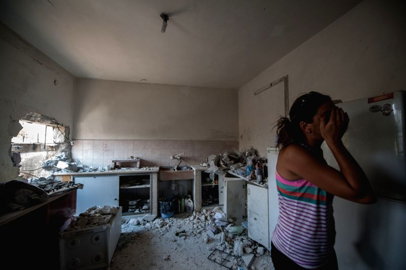 SDEROT (ISRAEL), July 21, 2014 A resident walks out of her kitchen damaged following a rocket attack by militants from Gaza, in Sderot, southern Israel bordering Gaza Strip, on July 21, ..